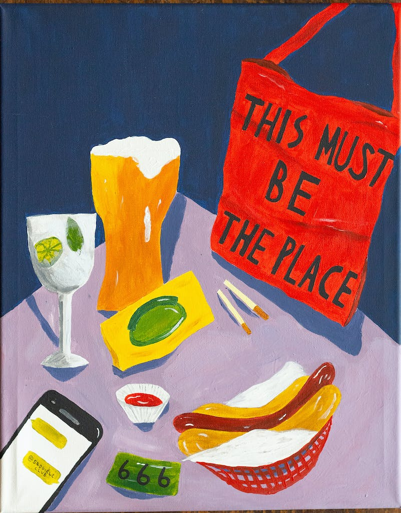 A painting of a table in The Hope & Ruin with a pint and a hot-dog